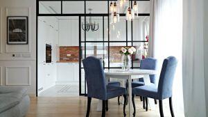 Właścicielom zależało na tym, żeby otworzyć kuchnię na salon, który przez to optycznie się powiększy, ale równocześnie chcieli mieć możliwość odseparowania miejsca do przygotowywania posiłków, tak żeby kuchenne zapachy nie rozchodziły się po całym domu. Architektka wpadła na genialny pomysł, oddzielenia kuchni od salonu szklaną ścianą, a właściwie dużymi drzwiami ze szkła. Projekt: Barbara Godawska (ihome Studio). Fot. Dekorian
