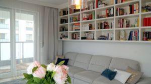 Właściciele mieszkania cenią sobie dobrą lekturę, nie wyobrażali więc sobie salonu bez choćby niewielkiej biblioteki na ścianie. Projekt: Barbara Godawska (ihome Studio). Fot. Dekorian