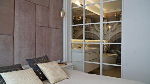 W części prywatnej właścicieli, w ich sypialni projektantka zdecydowała się zastosować podobnie rozwiązanie co w kuchni i w salonie. Przeszkloną ścianą ze stalowych profili, tym razem pomalowaną na biało, oddzieliła pokój od łazienki. Projekt: Barbara Godawska (ihome Studio). Fot. Dekorian