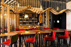 Soczyste czerwienie i zielenie na ścianie, ale także aksamitne obicia krzeseł, heksagonalne stoły, kształt modułów sufitu podwieszanego czy żyrandole – wszystkie te elementy nawiązują do motywu przewodniego projektu. Projekt: 3DPROJEKT architektura. Fot. Urszula Czapla