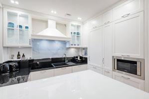 Klasyczna kuchnia została zaaranżowana w bieli. Gładkie fronty szafek zdobią dyskretne frezowania, które podkreślają styl apartamentu i nawiązują do detali architektonicznych starej kamienicy. Projekt: Izabela Kubicka (Qubus Architekci). Fot. Dekorian Home