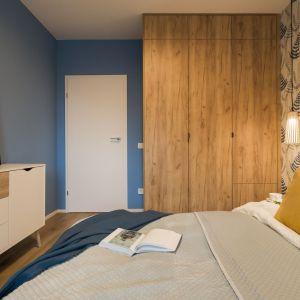 W sypialni ciekawym zabiegiem okazało się przeniesienie jednej z barw tapety na przeciwległą ścianę. Projekt i zdjęcia: KODO Projekty i Realizacje