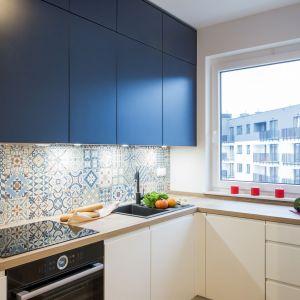 W kuchni barwne fronty górnych szafek wyróżniają się na tle jasnej zabudowy i drewnianych blatów. Projekt i zdjęcia: KODO Projekty i Realizacje