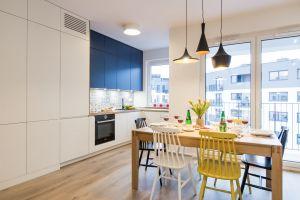 Kolorowe krzesła i barwne fronty górnych szafek wyróżniają się na tle jasnej zabudowy i drewnianych blatów. Projekt: KODO. Fot. Piotr Czaja