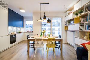 Geometria oraz wyraziste barwy dobrze czują się w zestawieniu z bielą i naturalnym materiałem. Widać to na przykładzie kuchni, w której kolorowe krzesła i barwne fronty górnych szafek wyróżniają się na tle jasnej zabudowy i drewnianych blatów. Projekt: KODO. Fot. Piotr Czaja