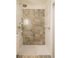 Patchworkowy wzór znalazł zastosowanie nie tylko na podłodze, ale także w strefie prysznicowej – na jednej ze ścian i we wnękach. Projekt: KODO. Fot. Piotr Czaja