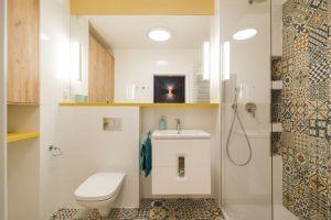 Szczególny zachwyt wzbudza łazienka. Jest przemyślana w każdym detalu, a dodatkowego uroku nadają jej wnęki, podkreślone za pomocą patchworkowego wzoru płytek. Projekt: KODO. Fot. Piotr Czaja