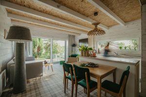 Ciepły, przyjazny dom dziadków przypominają meble z niego zachowane - stół i krzesła z zielonym obiciem. Projekt: Monika Buśko-Kuś. Fot Jakub Jakubicki