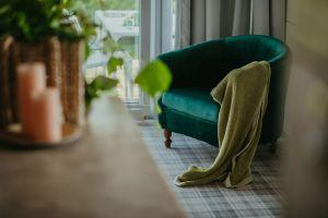 Z meblami dziadków koresponduje pluszowy fotel, miękkie tkaniny, zieleń we wnętrzu i ta, którą widać przez wielkie okna. Projekt: Monika Buśko-Kuś. Fot Jakub Jakubicki