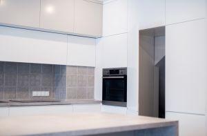 Sprytnie ukryte drzwi w zabudowie kuchennej - pomiędzy lodówką a piekarnikiem prowadzą do obszernej spiżarni pod schodami. Projekt i zdjęcie: Joanna Ochota