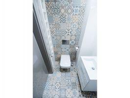 Aranżację niewielkiej toalety urozmaica patchworkowy wzór płytek, płynnie przechodzący z podłogi na jedną ze ścian. Projekt i zdjęcie: Joanna Ochota