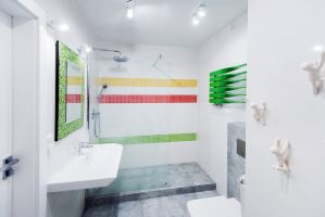 Projektantka zadbała jednak, by nie było nudno - rodzinną łazienkę ożywia mozaika w formie kolorowych pasów wyraźnie odcinających się od bieli ścian oraz intensywnie zielony grzejnik. Projekt i zdjęcie: Joanna Ochota
