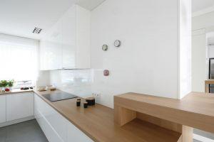 Granicę między kuchnią a salonem stanowi niewielki bar śniadaniowy. Projekt: Joanna Ochota. Fot. Bartosz Jarosz
