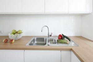Zabudowę kuchenną w białym kolorze wizualnie ociepla drewniany blat. Projekt: Joanna Ochota. Fot. Bartosz Jarosz