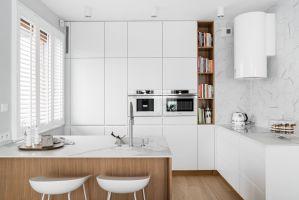 Skoncentrowana na jednej ścianie, minimalistyczna, wysoka zabudowa mieści niezbędny w nowoczesnej kuchni sprzęt AGD i akcesoria. Projekt: MAKA studio. Fot. Foto&Mohito