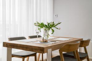 Choć to mieszkanie dla singla, nie mogło w nim zabraknąć dużego stołu, przy którym właścicielka swobodnie może ugościć nawet sześć osób. Projekt: MAKA studio. Fot. Foto&Mohito