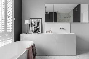 Niemała jak na tego typu pomieszczenie powierzchnia (10 m2) i rozciągające się niemal na całą wysokość okno, pozwoliły stworzyć komfortowy i szykowny salon kąpielowy. Projekt: MAKA studio. Fot. Foto&Mohito