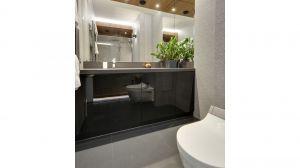 Rysunek drewna zdobiący przestronną strefę prysznica i strukturalne płytki niczym z kamienia nadały niewielkiej łazience wyjątkowy charakter. Projekt: Małgorzata Mataniak-Pakuła. Fot. Radosław Sobik