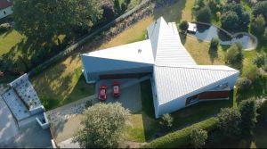 Inspiracją dla bryły domu stał się kształt działki, przypominający trapez, a także sama idea wyraźnego wydzielenia stref funkcjonalnych. W efekcie powstał trójskrzydłowy rzut inspirowany wiatrakiem. Projekt i zdjęcie: 3DPROJEKT architektura