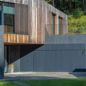 Wykończony grafitowym łupkiem parter jest częściowo ukryty w stoku. Jego ciemny kolor podkreśla jasne drewno zastosowane na fasadzie pierwszego piętra i na nieregularnym, dwuspadowym dachu. Projekt: Arūnas Liola, pracownia Arches. Fot. Evaldas Lasys