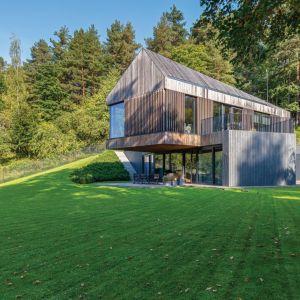 Zbudowany na wzgórzu dom sprawia wrażenie, jakby był zawieszony nad doliną, którą można podziwiać przez duże okna otwierające fasadę na przestrzeń. Projekt: Arūnas Liola, pracownia Arches. Fot. Evaldas Lasys