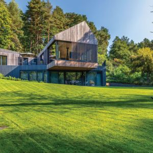 Całość pozostaje w harmonii ze wzgórzami i sosnami, nawiązuje do starych, drewnianych domów, jakie jeszcze można spotkać na litewskich wsiach. Projekt: Arūnas Liola, pracownia Arches. Fot. Evaldas Lasys