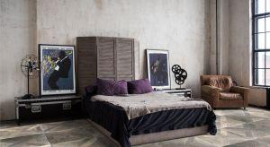 W modnie urządzonej sypialni króluje luksusowe łoże z tapicerowanym zagłówkiem w modnych głębokich kolorach w otoczeniu industrialnych elementów aranżacji, jak cegła, beton czy stal.