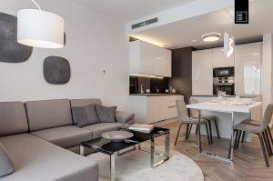 Kontrastowa kuchnia płynnie łączy się z salonem dzięki wyspie wpisanej w koncept stołu. Projekt i zdjęcia: Pracownia Wnętrz KODO