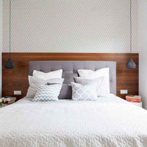 Tutaj zdecydowano się wyodrębnić z pomieszczenia garderobę, co znacznie uszczupliło powierzchnię sypialni. Króluje w niej łóżko z tapicerowanym zagłówkiem, stojące przy ścianie, obłożonej częściowo fornirowaną płytą. Po jego bokach zostało niewiele miejsca – wstawiono więc tam tylko niewielkie stoliki, na których nie zmieściłyby się lampki. Stąd pomysł na nisko zwijające lampy sufitowe. Ich światło nie razi w oczy osoby leżące w łóżku i jest odpowiednie do czytania. Fot. MGN Pracownia Architektoniczna
