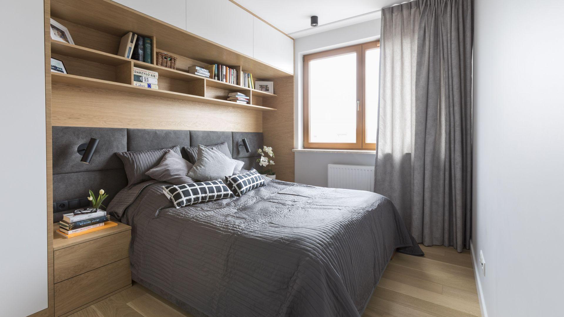 Gdy pomieszczenie jest niewielkie, na schowki warto wykorzystać wolne miejsce na ścianie, przy której stoi łóżko. Tak zrobiono tutaj. Nad szerokim, tapicerowanym wezgłowiem zbudowano półki, nad nimi, pod sufitem, szafki, a z boku, za szafką nocną – wąską szafę. Tym sposobem powstała wnęka, która po wyłożeniu drewnem wygląda bardzo zacisznie i przytulnie. Fot. MGN Pracownia Architektoniczna