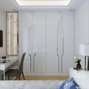 Ta sypialnia jest przykładem perfekcyjnie wykorzystanego miejsca. Jedną ze ścian zabudowano szafą, w którą wkomponowano  podświetlane półki ze szkła z przeznaczeniem na książki i dokumenty. Obok stoi lekkie biurko – to miejsce do pracy, a zarazem toaletka. Funkcjonalność to nie jedyna cecha tego pomieszczenia. Panuje w nim bowiem bardzo przytulny, zachęcający do odpoczynku klimat. Tworzą go dekoracyjne elementy wystroju – nastrojowe oświetlenie, miękkie tkaniny, srebrne wzory na frontach mebli i inne. Apartament w Centrum. Fot. Yassen Hristov/Hompics