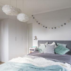Nawet w oszczędnie urządzonym wnętrzu może panować miła atmosfera. Do tej funkcjonalnie urządzonej sypialni przytulność wprowadzają lampy z puchatymi abażurami, girlanda świetlna na ścianie i miękkie tkaniny na łóżku. Żeby zaoszczędzić miejsce na pojemne schowki, którymi zagospodarowano większą część bocznej ściany, zrezygnowano z tradycyjnych drzwi. Zastąpiono je suwanymi, chowającymi się za plecami szafy. Fot. MGN Pracownia Architektoniczna