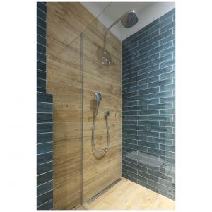 Płytki ceramiczne o formacie drewna obecna są zarówno na ścianie, jak i podłodze, zastępując brodzik prysznicowy. Projekt: Maciejka Peszyńska-Drews. Fot. Bartosz Jarosz