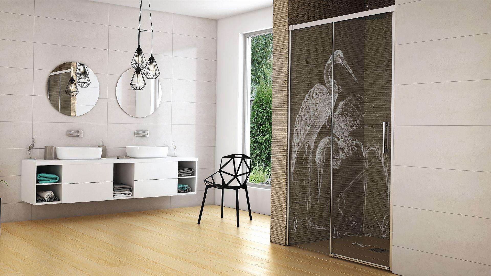 Dekoracyjny wzór wykonywany metodą laserowego graweru na szkle kabiny prysznicowej przedstawiający brodzące w wodzie żurawie. Fot. Radaway