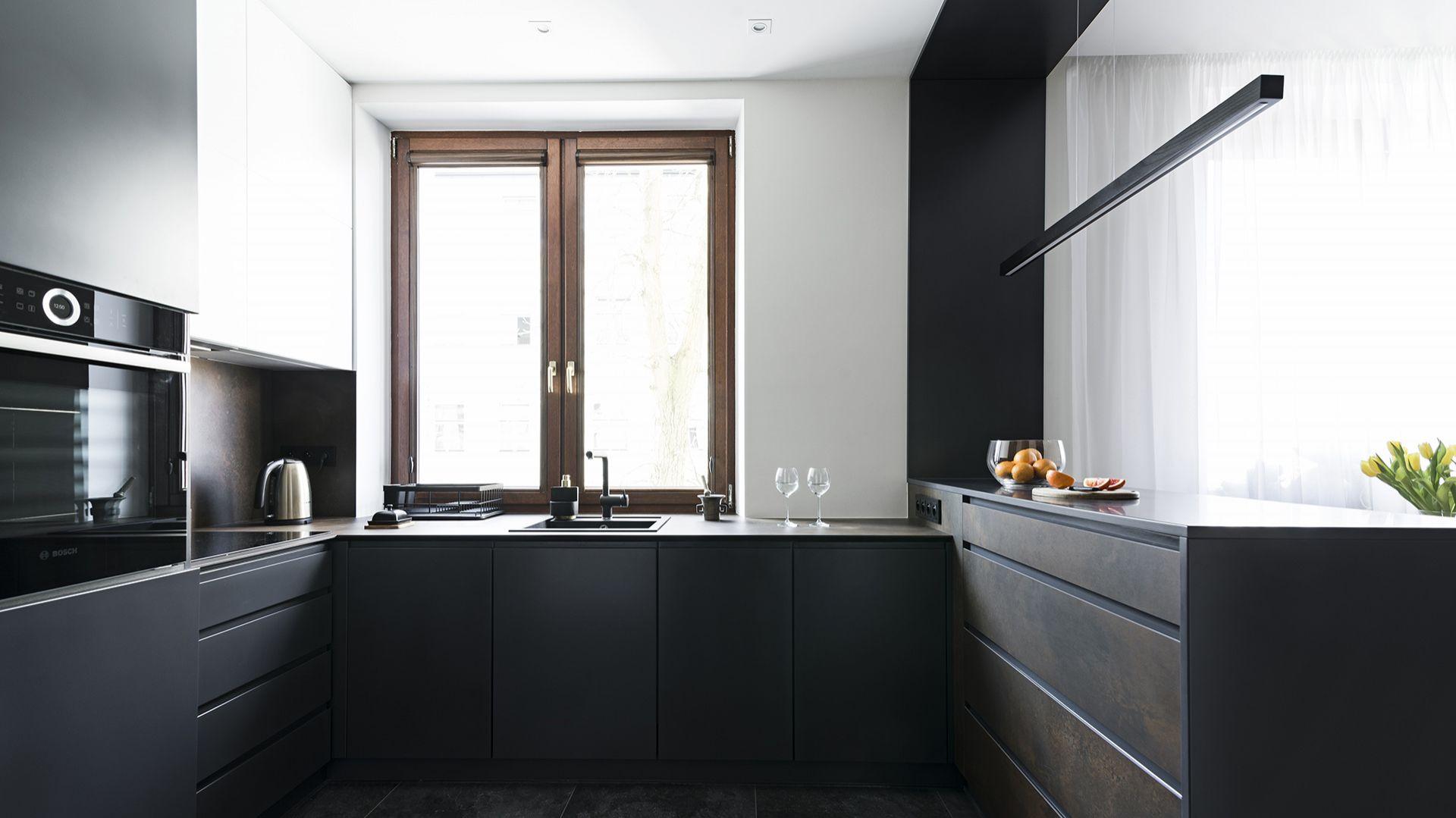 Kuchnia – połączenie grafitowych lakierowanych frontów z rudo-brunatnym spiekiem kwarcowym – dopełnione oświetleniem stanowi niepowtarzalną całość. Projekt: MMA Pracownia Architektury. Fot. Rafał Chojnacki