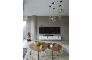 Inne autorskie rozwiązania w przestrzeni dziennej to szafka RTV  i okrągłe, drewniane stoliki. Projekt: Monika i Adam Bronikowscy (HOLA Design). Fot. Yassen Hristov