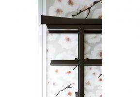 W Japonii Torii często jest stawiane w przydomowym ogrodzie, stąd piękna fototapeta z motywem kwitnącej wiśni. Zdobi ona całą ścianę, wnosząc do aranżacji element z natury. Projekt: Monika i Adam Bronikowscy (HOLA Design). Fot. Yassen Hristov