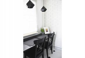 Stylowy, czarny stół stanął pod oknem w korytarzu, tuż obok kuchni. Projekt i zdjęcia: Dominika Wojciechowska (NIDUS Interiors)