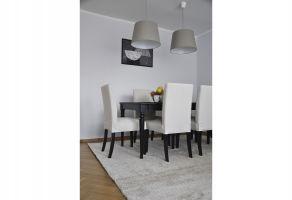 W salonie wygospodarowano miejsce na duży stół, przy którym domownicy mogą wygodnie zjeść i przyjmować przyjaciół. Projekt i zdjęcia: Dominika Wojciechowska (NIDUS Interiors)