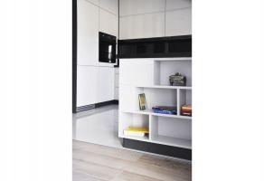 Przestrzeń kuchni oddziela od części wypoczynkowej półwysep, oferujący dodatkową przestrzeń do przechowywania i wyeksponowania bibelotów. Projekt i zdjęcia: Dominika Wojciechowska (NIDUS Interiors)
