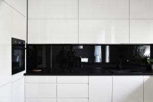 Pojemna zabudowa kuchni ma minimalistyczną, czarno-białą formę. Projekt i zdjęcia: Dominika Wojciechowska (NIDUS Interiors)