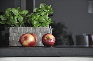 Minimalistyczną, czarno-białą zabudowę kuchni ożywiają sezonowe dodatki. Projekt i zdjęcia: Dominika Wojciechowska (NIDUS Interiors)
