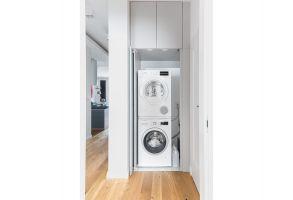 Korytarze przeprojektowano po to, by pomieścić dodatkowe funkcje. W jednym z nich udało się ulokować funkcjonalną pralnię. Projekt: Dominika Wojciechowska (NIDUS Interiors). Fot. Pion Poziom