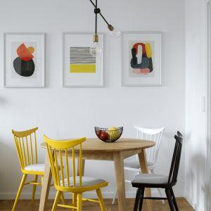 Kącik z drewnianym stołem przytula się do obu stref i pełni podwójną funkcję – jest miejscem codziennych posiłków oraz wygodnym aneksem jadalnym w salonie, gdy gospodarze przyjmują gości. Projekt: Biuro architektoniczne Madama. Fot.  Yassen Hristov