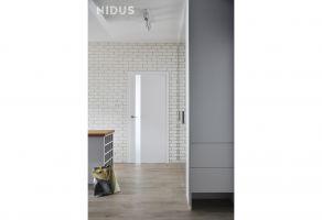Nietypowy dla współczesnej zabudowy mieszkaniowej układ z ogromnym korytarzem poprzedzającym wejście do salonu skłonił do rezygnacji z kilku ścian. Projekt: Dominika Wojciechowska (NIDUS Interiors).
