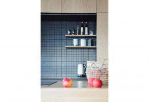 Przestrzeń nad blatem w kuchni wykończona matowymi czarnymi płytkami, pięknie odcina się na tle zabudowy w kolorze jasnego dębu. Projekt: Dominika Wojciechowska (NIDUS Interiors)