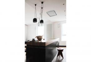 Z sufitu nad częścią roboczą wyspy zwieszają się tylko czarne lampy, przypominające reflektory. Ten dekoracyjny element wystroju z pogranicza stylistyki retro i loft, odnajdziemy także w sypialni i w łazience. Projekt: Dominika Wojciechowska (NIDUS Interiors)