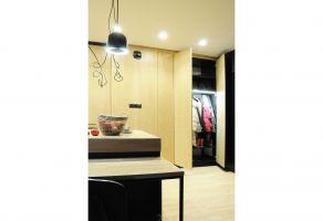 Ściana kuchennej zabudowy płynnie przechodzi w funkcjonalną garderobę skrywającą szafę i szafkę na buty. Projekt: Dominika Wojciechowska (NIDUS Interiors)