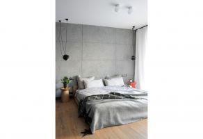 Betonowe płyty na ścianie za łóżkiem nadają wnętrzu mocniejszy, loftowy pazur. Projekt: Dominika Wojciechowska (NIDUS Interiors)