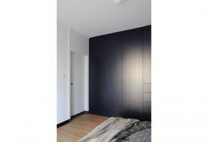 Obszerna zabudowa w sypialni pełni funkcję garderoby. Projekt: Dominika Wojciechowska (NIDUS Interiors)